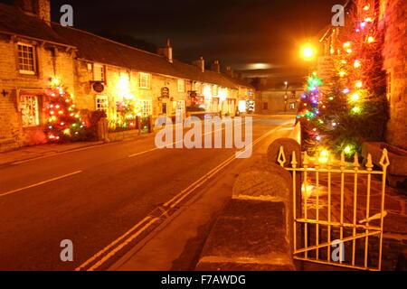 Beneath a full moon,Christmas trees illuminate the main street in Castleton, a village in the Peak District Derbyshire - Stock Photo