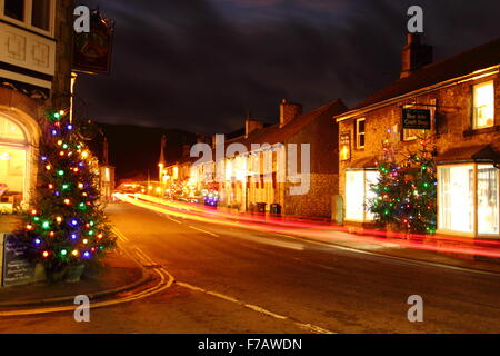 Christmas trees hung with fairy lights, illuminate the main street in Castleton, a village in the Hope Valley, Peak - Stock Photo