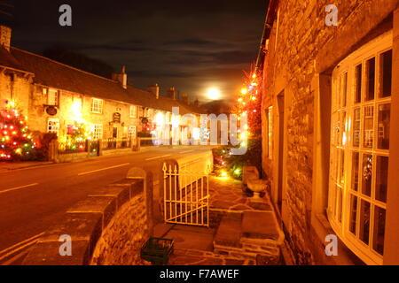 Beneath a full moon,Christmas trees illuminate the main street in Castleton, Peak District National Park, Derbyshire - Stock Photo