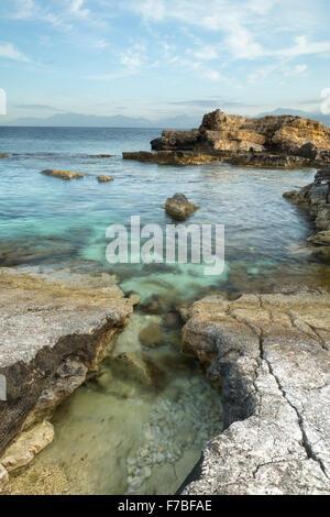 The rocks on Kanoni beach, Kassiopi, Corfu are lit up with the orange light of sunrise in the Straits of Corfu. - Stock Photo