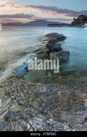 The rocks on Kanoni beach, Kassiopi, Corfu are lit up with the orange light of sunrise. - Stock Photo