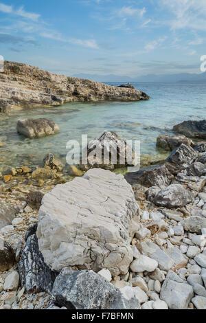 Pebbles and rocks on a beach at Kassiopi, Corfu, at sunrise. - Stock Photo