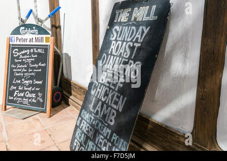 Signs outside an English pub in a Spanish holiday resort advertising Sunday Roast and other English meals. - Stock Photo