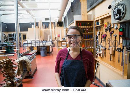Portrait confident female high school student in workshop - Stock Photo