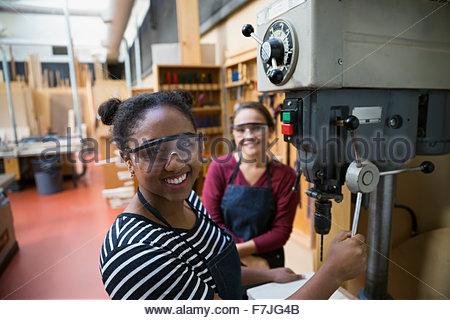 Portrait confident female high school students using drill - Stock Photo