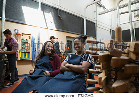 Female high school students laughing in workshop - Stock Photo