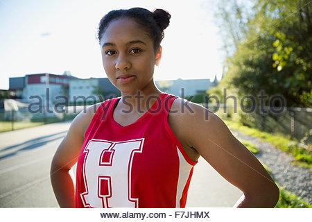 Portrait confident high school athlete on running track - Stock Photo