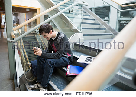 High school student texting on school stairs - Stock Photo