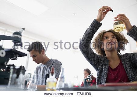 High school student dropping liquid into beaker - Stock Photo