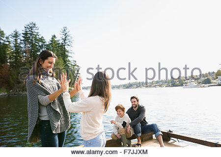 Family playing on lake dock - Stock Photo