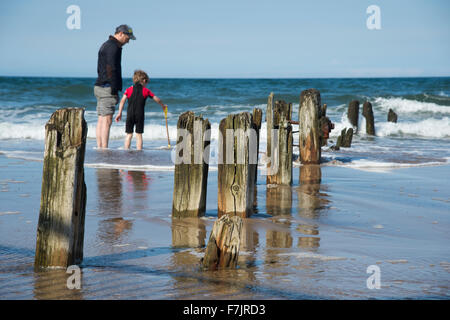 Sandsend beach (North Yorkshire Coast, England) in summer - father & son paddle as waves from the sea lap the shore - Stock Photo