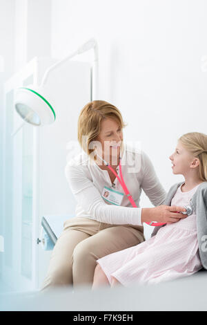 Pediatrician using stethoscope on girl patient in examination room - Stock Photo