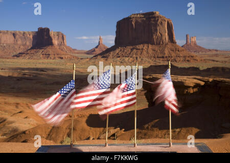 US Flags blowing in wind in front of red buttes and colorful spires of Monument Valley Navajo Tribal Park, Southern - Stock Photo