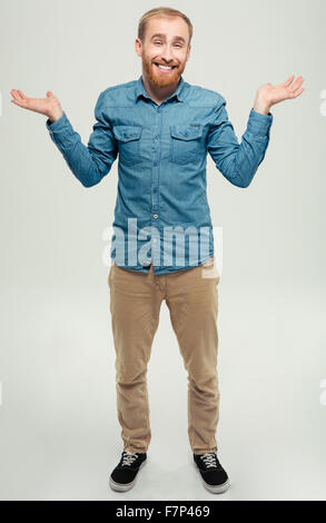 Full length portrait of a smiling casual man shrugging shoulders isolated on a white background - Stock Photo