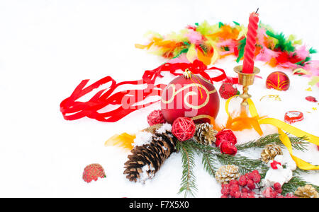 Christmas toys and jewelry on snow from candles - Stock Photo