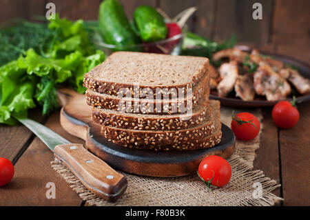 Wholegrain rye bread with bran and seeds on wooden table, healthy eatin - Stock Photo