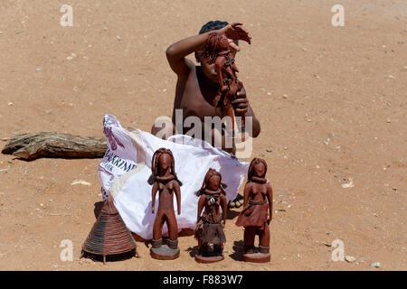 NAMIBIA, KAMANJAB, OCTOBER 10: Himba child with souvenirs for sale in the Himba village in northern Namibia, near - Stock Photo