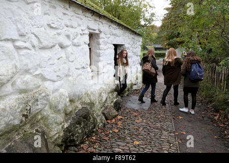 Young women visiting a stone whitewashed cottage at St Fagans Museum of Welsh Life in Cardiff South Wales UK  KATHY - Stock Photo