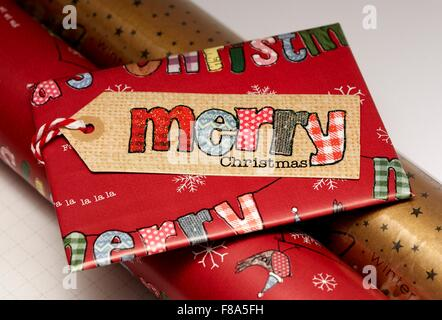 A small Christmas present wrapped in red paper with a merry Christmas label - Stock Photo