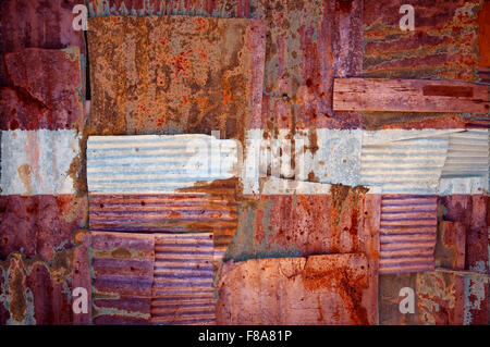 An abstract background image of the flag of Latvia painted on to rusty corrugated iron sheets overlapping to form - Stock Photo