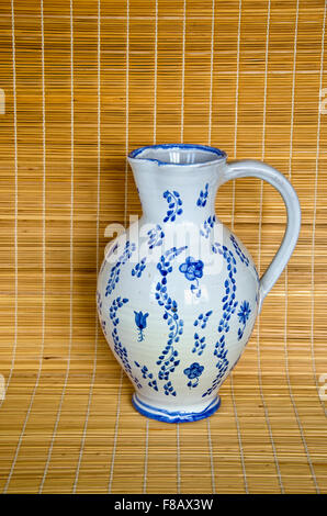 White and blue jug on bamboo material background - Stock Photo