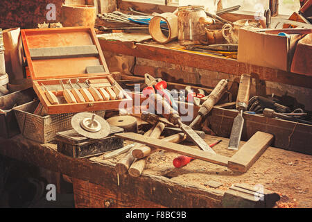 Retro stylized old tools on wooden table in a joinery. - Stock Photo