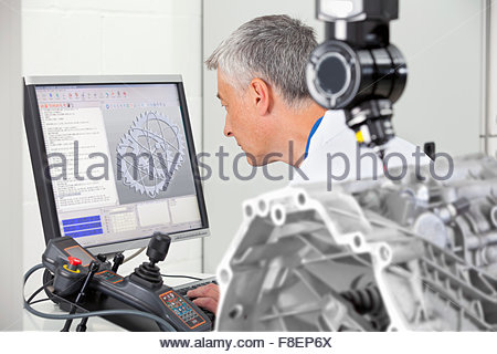 Engineer working at computer behind probe scanning engine block - Stock Photo