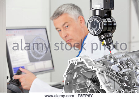 Engineer working at computer and turning toward probe scanning engine block - Stock Photo