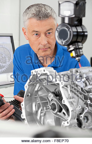 Engineer with joystick controlling probe scanning engine block - Stock Photo