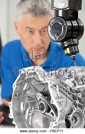 Close up of engineer with joystick controlling probe scanning engine block - Stock Photo