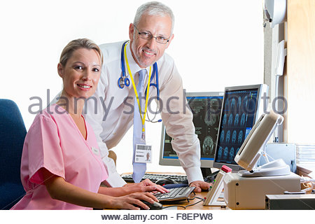 Portrait confident doctor and nurse reviewing digital brain scan in doctor - Stock Photo