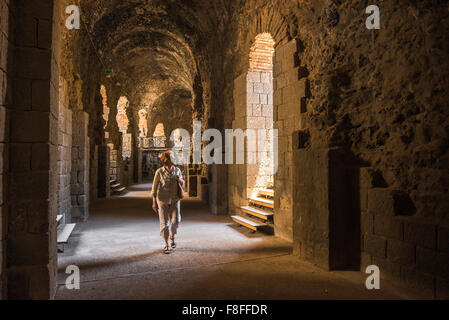 Woman travel solo, a middle aged female tourist in Catania explores the subterranean corridor beneath the ancient - Stock Photo