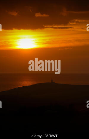 A Sunset over Belle Tout lighthouse near Beachy Head on the South Downs in Sussex, United Kingdom - Stock Photo