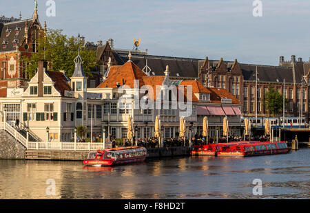 Tour Boats next to tourist office near Central railway Station in Amsterdam Holland - Stock Photo