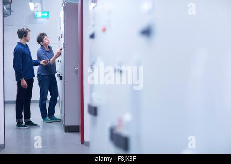 Colleges in control room looking at switchgear - Stock Photo