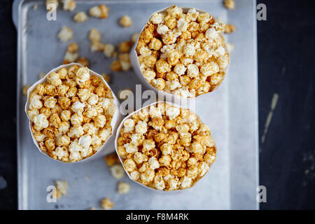 Tree paper bags full of popcorn on metal background - Stock Photo