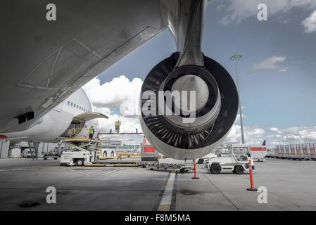 Rear view of A380 jet engine with ground crew loading freight - Stock Photo