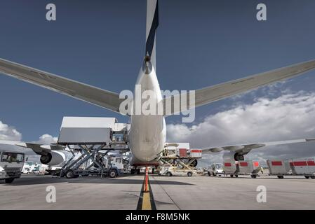 Rear view of A380 jet aircraft being loaded at airport - Stock Photo
