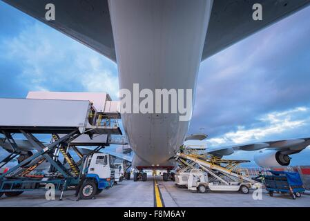 Ground crew loading A380 aircraft at airport - Stock Photo
