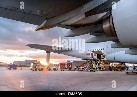 Ground crew loading A380 aircraft at sunset - Stock Photo