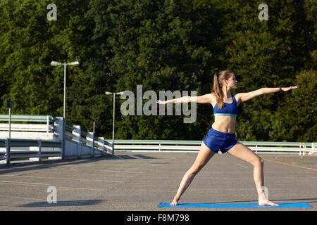 Young woman practicing yoga in urban parking lot - Stock Photo