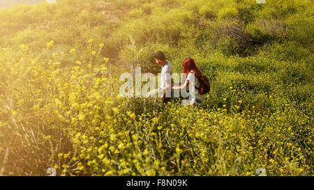 Shot of young couple walking through grass on a peak. Young man and woman hiking on a summer day. - Stock Photo