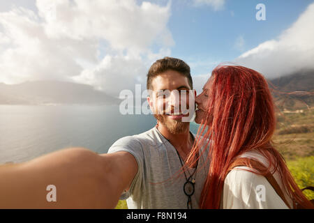 Young couple taking a selfie outdoors. POV shot man holding a camera and taking a self portrait with woman kissing - Stock Photo