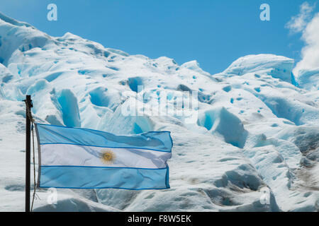 Argentine flag flying in front of the Perito Moreno Glacier in Argentina - Stock Photo