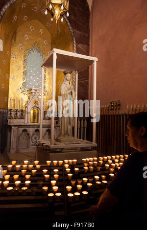 Prayer candles in the Basilica of our Lady of the Rosary in the Sanctuary of Our Lady of Lourdes - Stock Photo