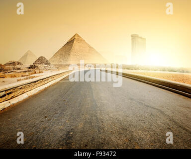 Asphalted road to pyramids and modern buildings of Giza - Stock Photo