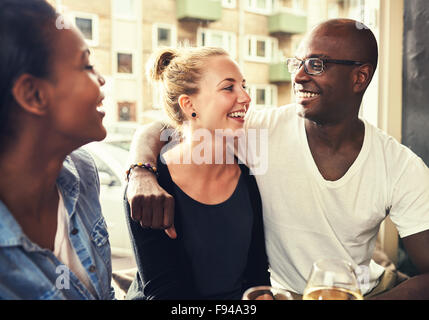 Multi ethnic couple smiling at each other - Stock Photo