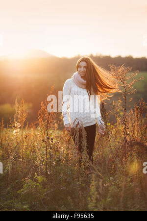 Outdoor portrait of beautiful woman in autumn meadow - Stock Photo