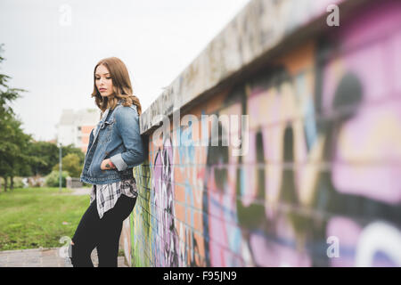 Knee figure of young handsome caucasian blonde straight hair woman posing leaning against a wall, hands in pocket, - Stock Photo