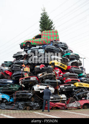Employees at a car junkyard have decorated a pile of dozens of junk cars like a Christmas tree in Hamburg, Germany, - Stock Photo